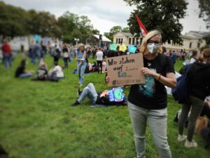 """Die Bloggerin mit einem Demo-Schild im Hofgarten Bonn. Auf de mSchild steht """"Wir stehen auf dünnem Eis..."""""""