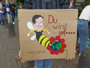 """Demo-Schild mit einer Armin Laschet Karikatur darauf. Er als Biene sticht eine Weltkugel und sagt """"Du wirst gef****"""""""